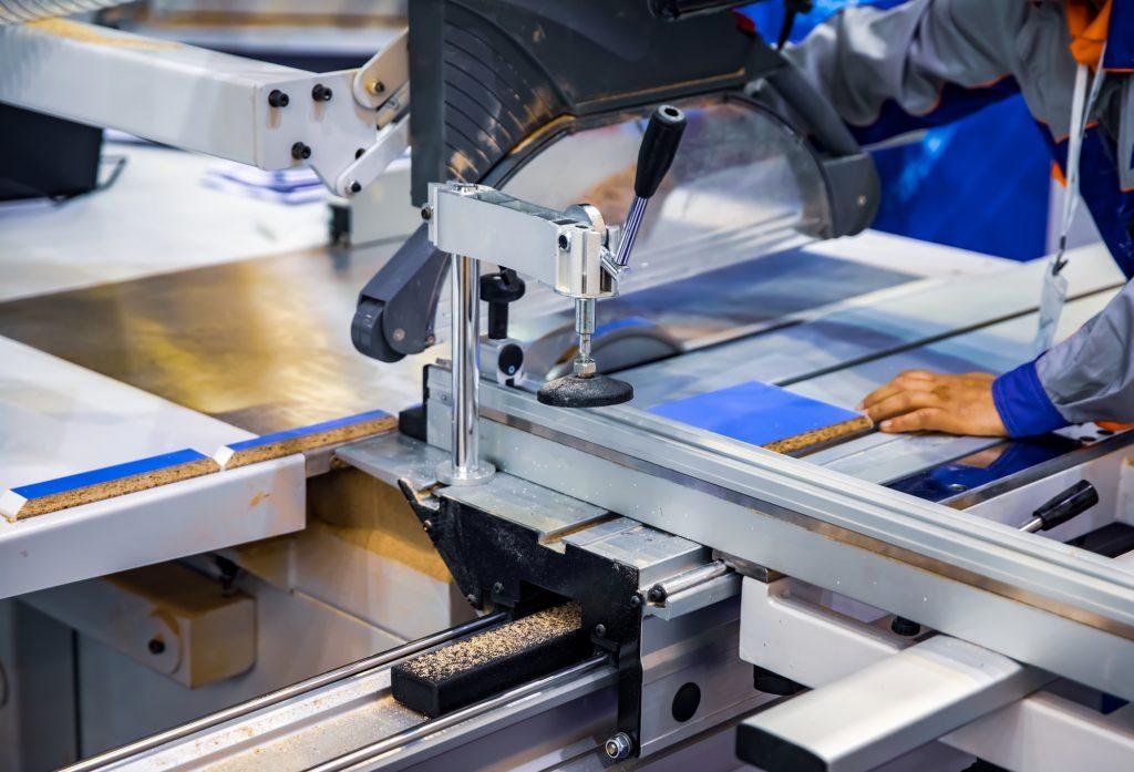 Carpenter worker operating wood cutting machine. CNC woodworking